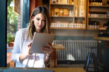 Wall Mural - Beautiful brunette girl using tablet for work, freelance, blogging, studying, shopping