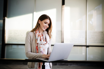 Wall Mural - Happy girl working online or studying and learning while using tablet