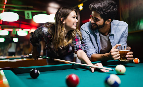 Happy young man playing snooker with his girlfriend. Happy loving couple.