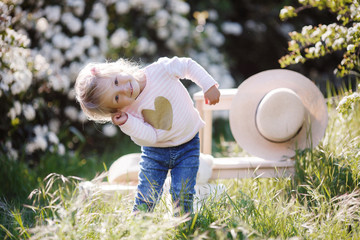 A cute little girl in a big straw hat spends time outdoors alone in a spring park park, sitting against a background of white flowering bushes. Spring portrait of a charming little girl walking park