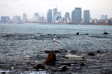 """An Israeli flag, attached to a rock known as """"Andromeda's Rock"""", flutters in the Mediterranean Sea as Tel Aviv's skyline of high-rise buildings is seen in the background, in Jaffa, Israel"""