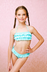 Portrait of cute smiling little girl child schoolgirl teenager in swimsuit isolated