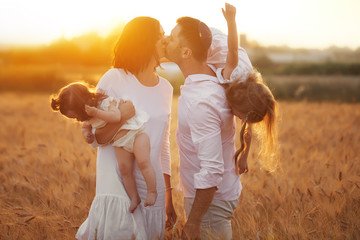 Happy Jewish family: mother, father and two child daughters on nature on sunset. Love and care concept