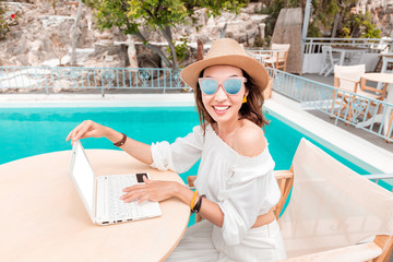 Girl copywriter or blogger working at a laptop on the background of the swimming pool at the resort. The concept of the modern remote freelancer job