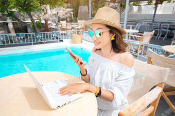 Happy asian woman wirking with mobile phone and laptop pc and relaxing near swimming pool. Distant work concept