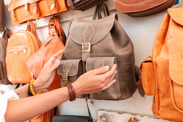 Girl buyer chooses a backpack on the market in the shop of leather Handicrafts