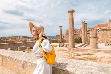 Happy asian Traveler with backpack walking in historical and archaeological site in Lindos Acropolis. Tourist attraction and ancient architecture in Greece
