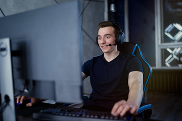 Professional gamer playing online video game at night time