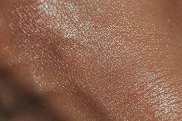 texture of human skin with liquid highlighter swatch