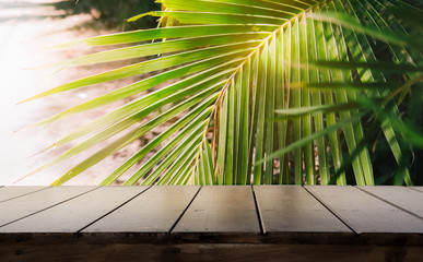 Dark wood table top (Bar) with blur on green palm leaves or tree in tropical forest with bokeh light at background