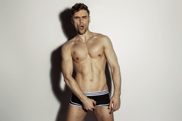 Strong stripped muscle male model in black underwear with white strips on white isolated font background with shadow