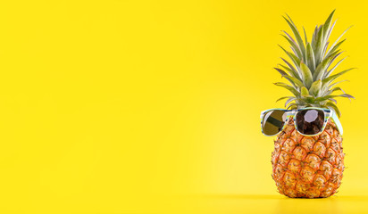 Creative pineapple looking up with sunglasses and shell isolated on yellow background, summer vacation beach idea design pattern, copy space close up