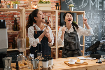 two asian happy girl worker colleagues with aprons enjoy dancing while listening to music in bakery. carefree young women waitress coworkers singing with songs in bar counter in modern coffee store