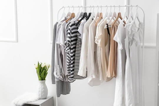 Rack with clean female clothes in dressing room