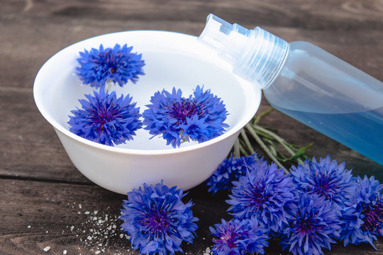 blue cornflowers lie in the water in a bowl near a bottle of cornflower water against the background of old boards.