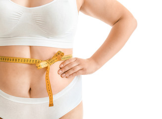 Plus size woman with measuring tape on white background. Concept of weight loss