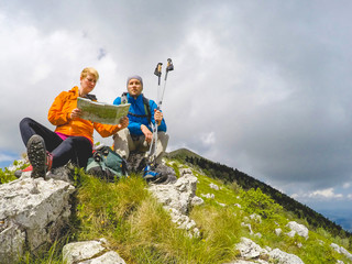 Two hikers sitting on the top of the Mountain