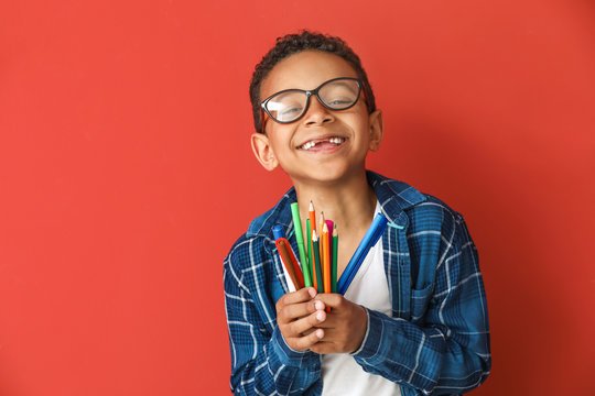 Cute African-American boy with pencils and markers on color background