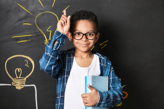 African-American boy with raised index finger near drawn light bulbs on dark wall