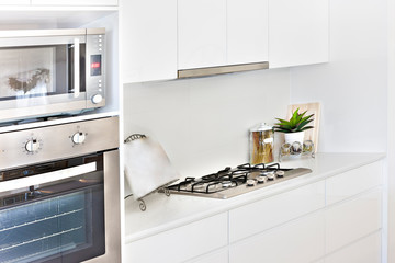 Modern Kitchen tools with white walls and oven.