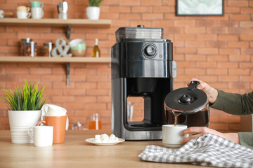 Beautiful woman using coffee machine in kitchen