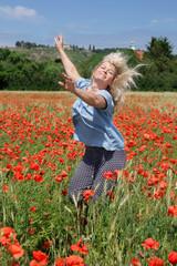 Ausgelassene, reife, hellblonde Frau springt in Mohnblumenfeld