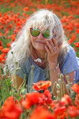 Portrait, reife, blonde Frau mit Sonnenbrille im Mohnfeld