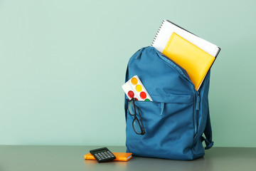 School backpack with stationery on table against color background