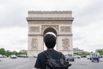 Wall Mural - a man with backpack looking at Arc de Triomphe, famous landmark and travel destination in Paris, France. Traveling in Europe in summer