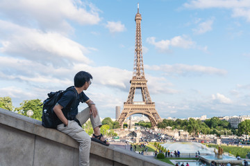Wall Mural - a man with backpack looking at Eiffel tower, famous landmark and travel destination in Paris, France. Traveling in Europe in summer