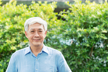 Headshot of happy old mature asian with white grey hair man wearing blue shirt smiling positive and looking at camera in garden outside the house. Senior asian male portrait with retirement concept.