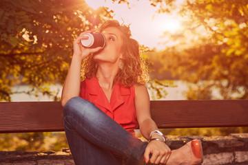 Beautiful woman drinking coffee and enjoying sunrise/sunset.