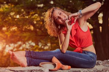 Woman holding heart shape and enjoying the sunset/sunrise.