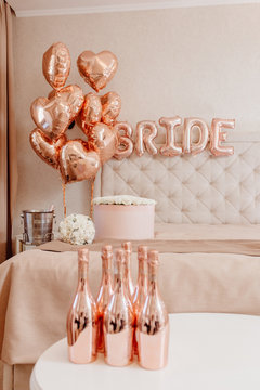 Elegance Interior of Hotel Room for Wedding Night. Bright Apartment Decorated Peach Color Helium Balloons and Bubble Word Bride on Wall, Bouquet of Roses on Honeymoon Bed and Bottle of Champagne
