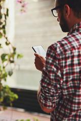 Modern man using cellphone outdoors.