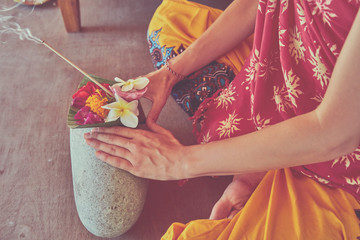 Woman holding canang sari - offering for Gods and praying. Balinese tradition.