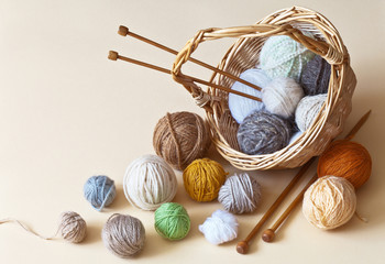 Yarn balls of wool for hand knitting in a wicker basket and knitting needles on a light background. Needlework, hobbies and crafts. Closeup, still life, copy space