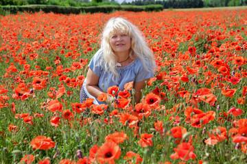 Glückliche, blonde, reife Frau entspannt im Mohnblumenfeld