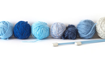 The balls of different shades of blue wool and acrylic yarn for hand knitting lie in a row on a white background. Bottom and top empty space for text. Ckjseup, copy space