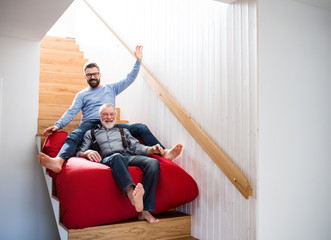 An adult hipster son and senior father indoors at home, having fun. Wall mural