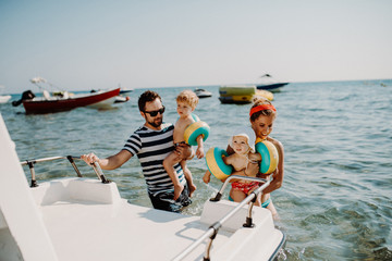 Parents with two small toddler children standing by boat on summer holiday.
