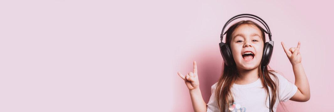 Cute little girl listening music wearing headphones.