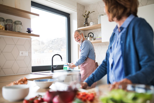 A portrait of senior couple indoors at home, cooking.