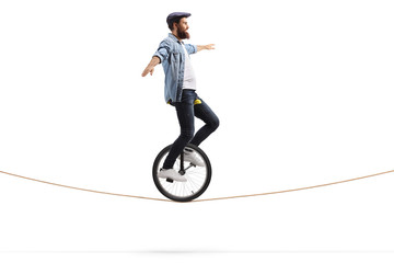 Young man riding a unicycle on a rope and balancing with hands Wall mural