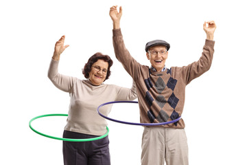 Male and female seniors with hula-hoops dancing