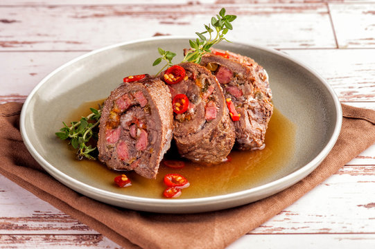 Beef tenderloin rolls stuffed. Slices of meat served on a plate in a sauce and with fresh vegetables and herbs. Close up and horizontal orientation.