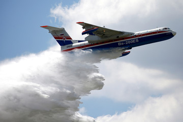 A Beriev Be-200ES firefighting airplane releases water during a flying display during the 53rd International Paris Air Show at Le Bourget Airport near Paris