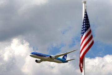 An Boeing 787-9 Dreamliner of Air Tahiti Nui flies past U.S. flag as it performs during the 53rd International Paris Air Show at Le Bourget Airport near Paris
