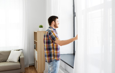 people concept - young man opening window curtain at home