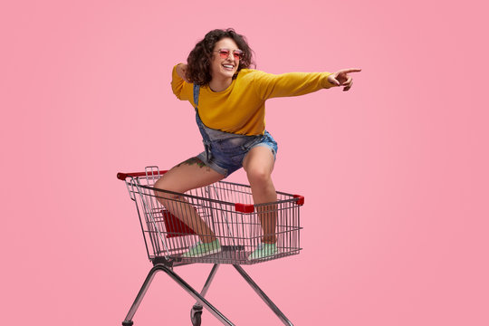 Cheerful young woman riding forward on shopping cart